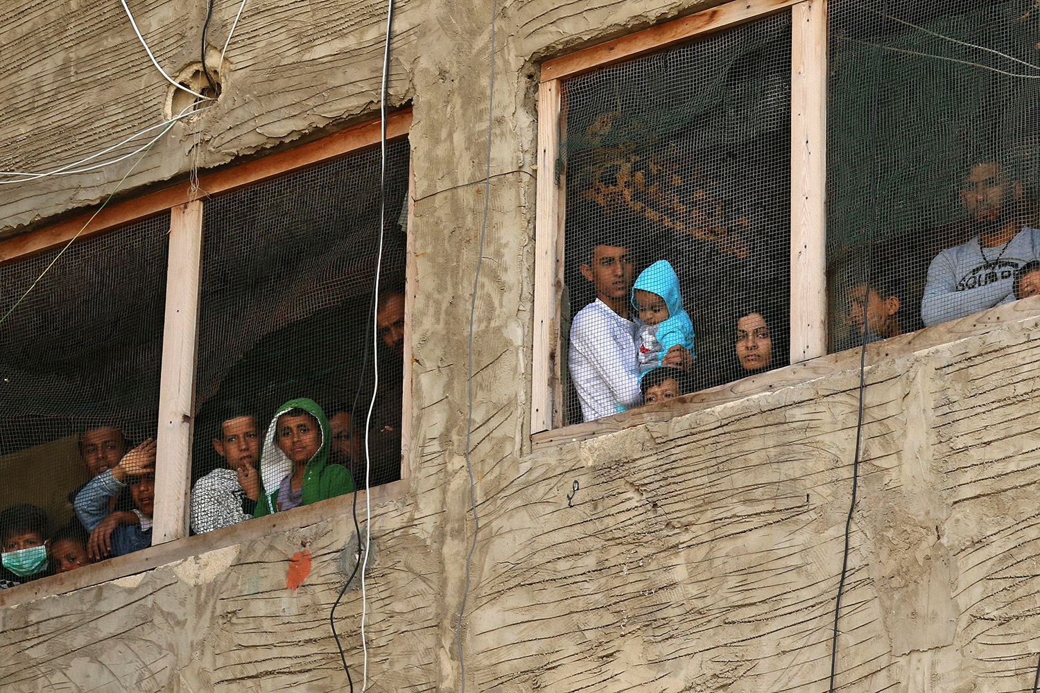 Syrian refugees look out the window of a building under construction—which they have been using as a shelter—in the city of Sidon, southern Lebanon, on March 17. MAHMOUD ZAYYAT/AFP via Getty Images