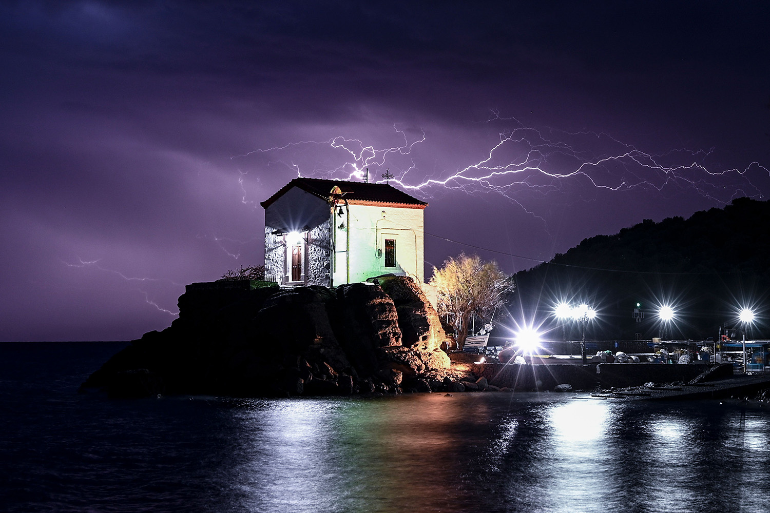 Lightning  strikes behind the chapel of Panagia Gorgona in the village of Skala Sykamias, north of Lesbos, on Feb. 27. ARIS MESSINIS/AFP via Getty Images