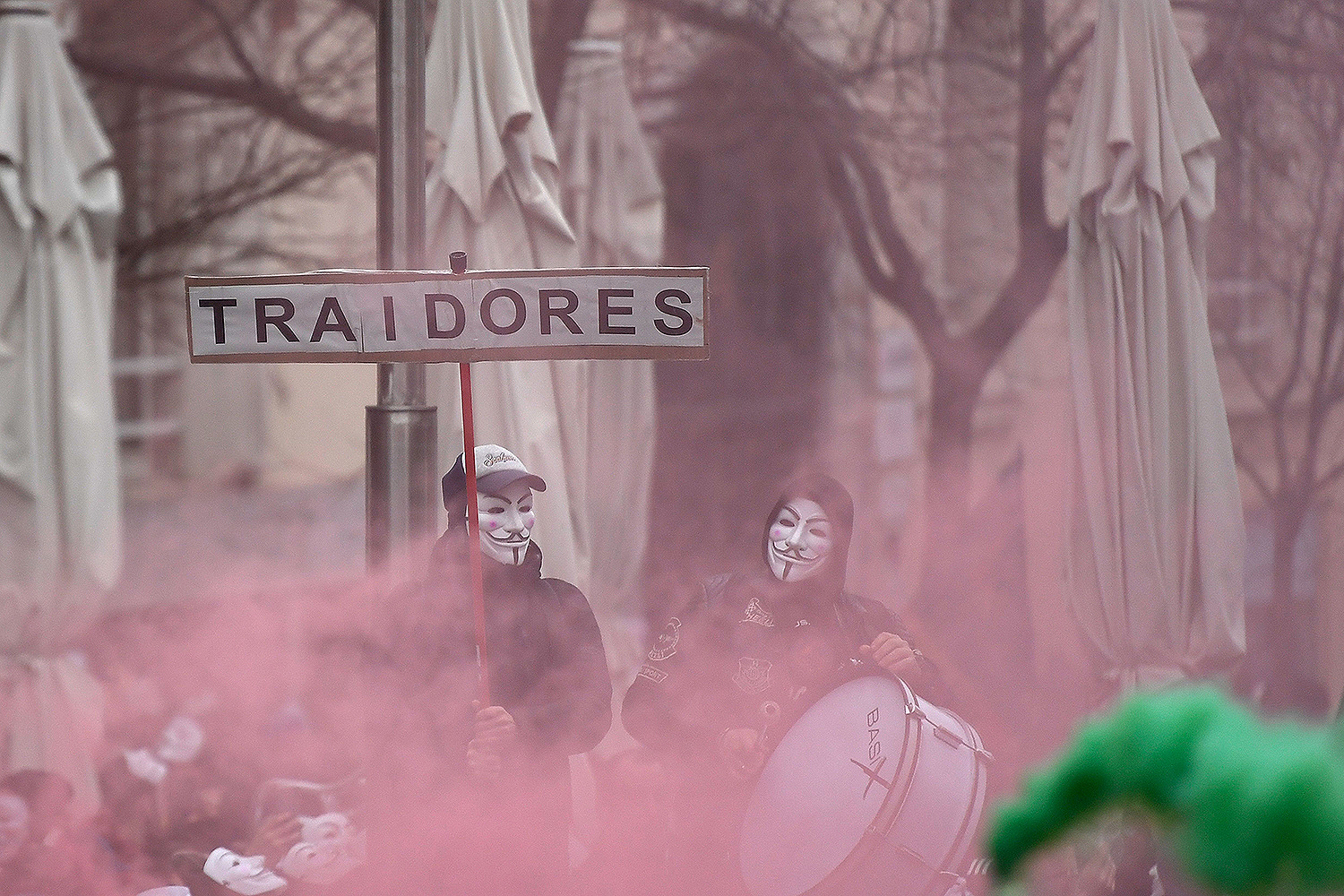 "Spanish policemen and civil guards sporting Guy Fawkes masks hold a ""Traitors"" placard near the entrance of the Parliament building in Madrid on March 3 during a demonstration to demand fair wages. OSCAR DEL POZO/AFP via Getty Images"