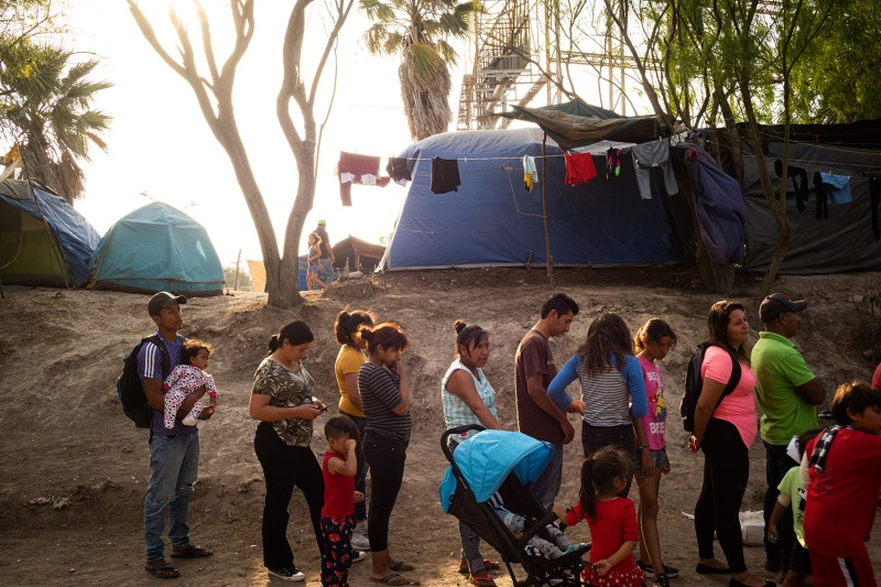 A group of migrants waits for food distribution inside the makeshift migrant camp in Matamoros, Mexico, on March 19.