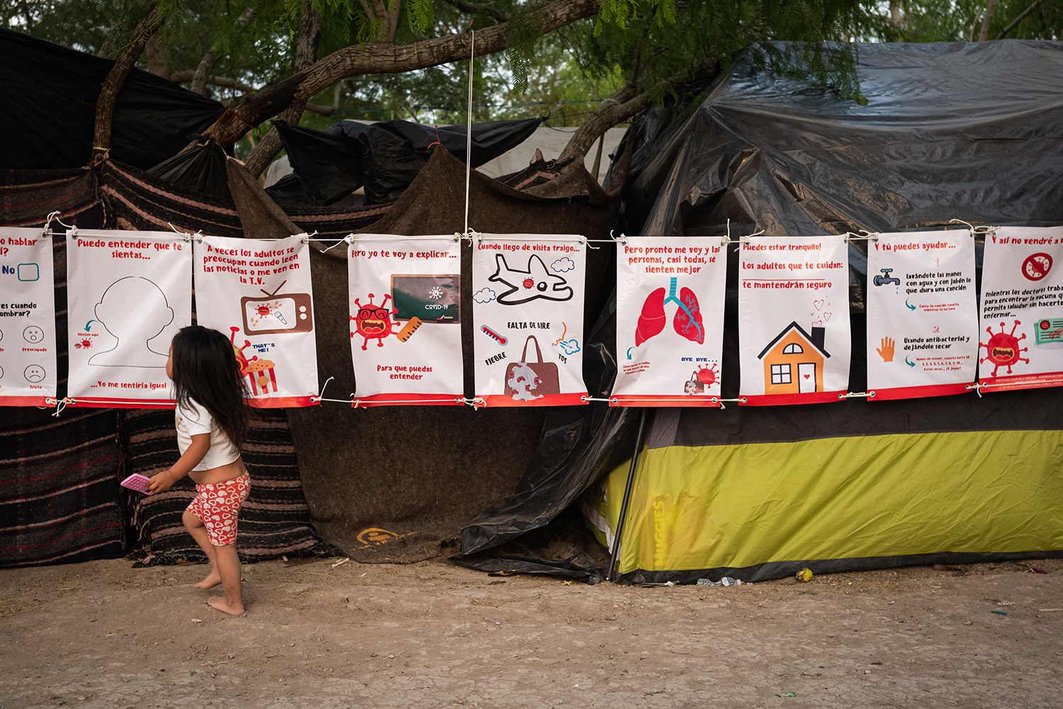 A girl runs past a series of signs explaining how the coronavirus spreads at the Matamoros refugee camp March 19.