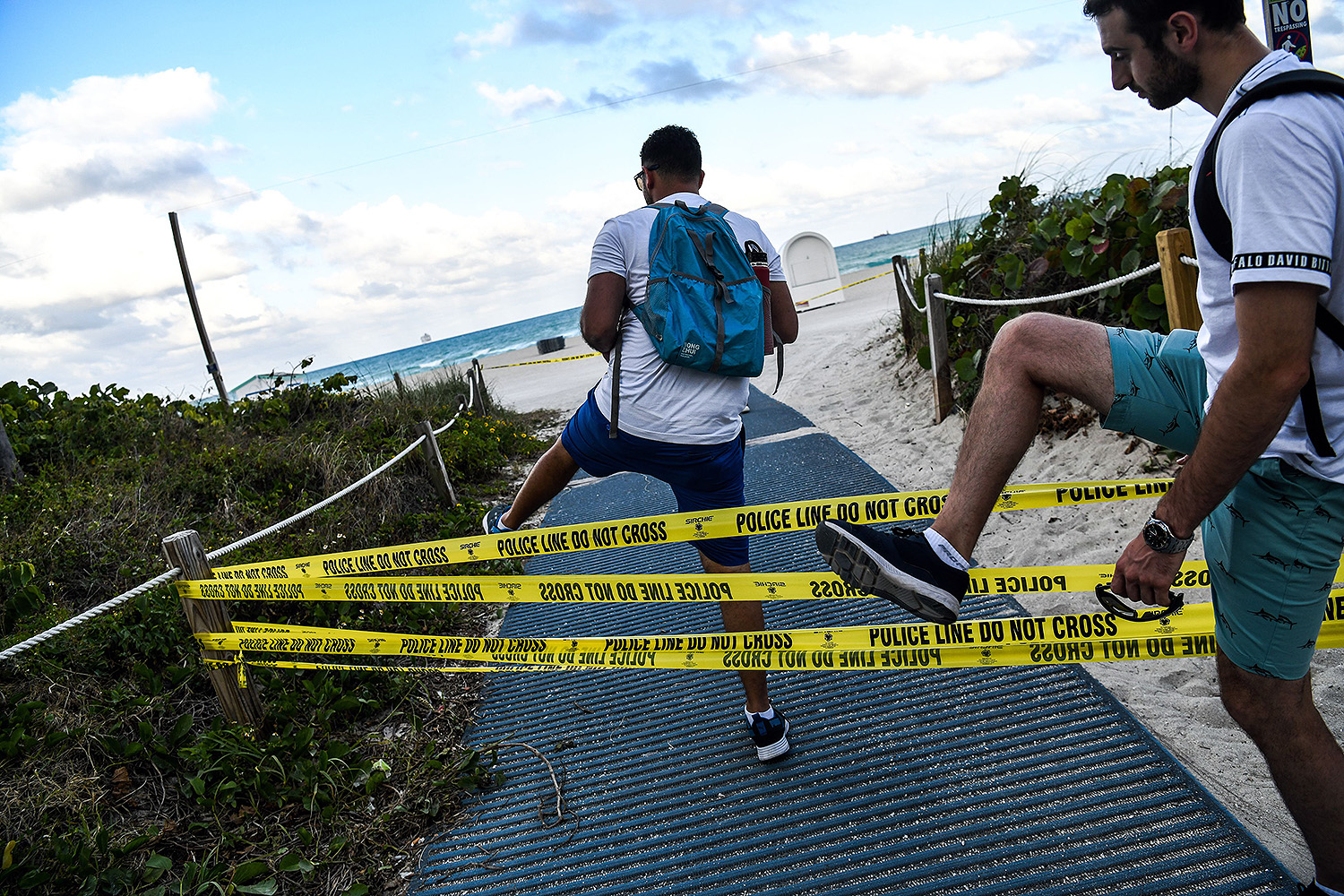 """Tourists trespass at the closed Miami Beach in Florida on March 19. After seeing large numbers of spring breakers crowd the shoreline, Miami Beach Mayor Dan Gelber closed all beaches in an attempt to stop the spread of the coronavirus. """"You've got to think about the person next to you and even the person you don't know,"""" Gelber said. CHANDAN KHANNA/AFP via Getty Images"""