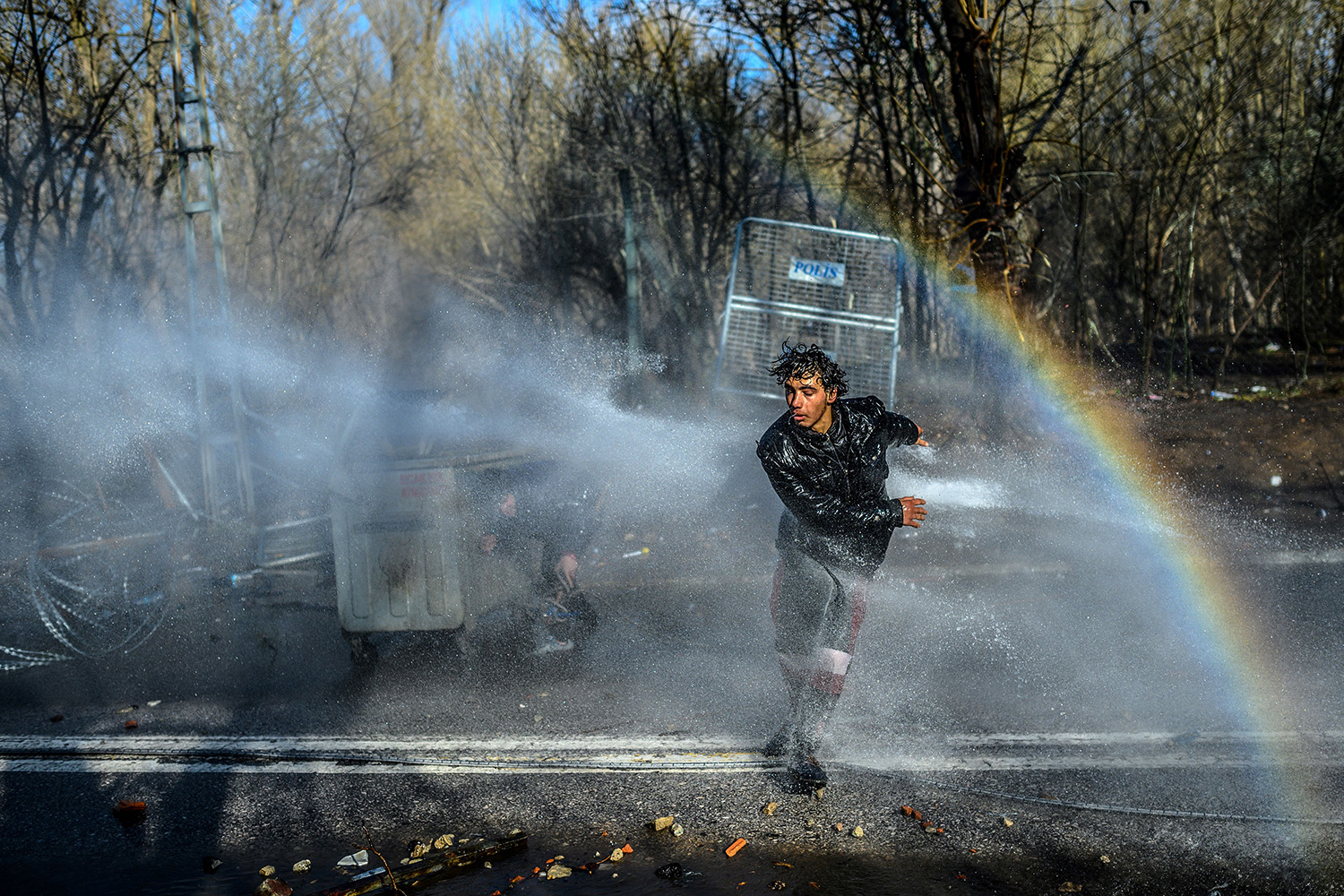 A migrant runs away and another takes cover behind a trash container as Greek police use water cannons to block them from breaking fences at the Turkey-Greece border in Edirne, Turkey, on March 7. BULENT KILIC/AFP via Getty Images