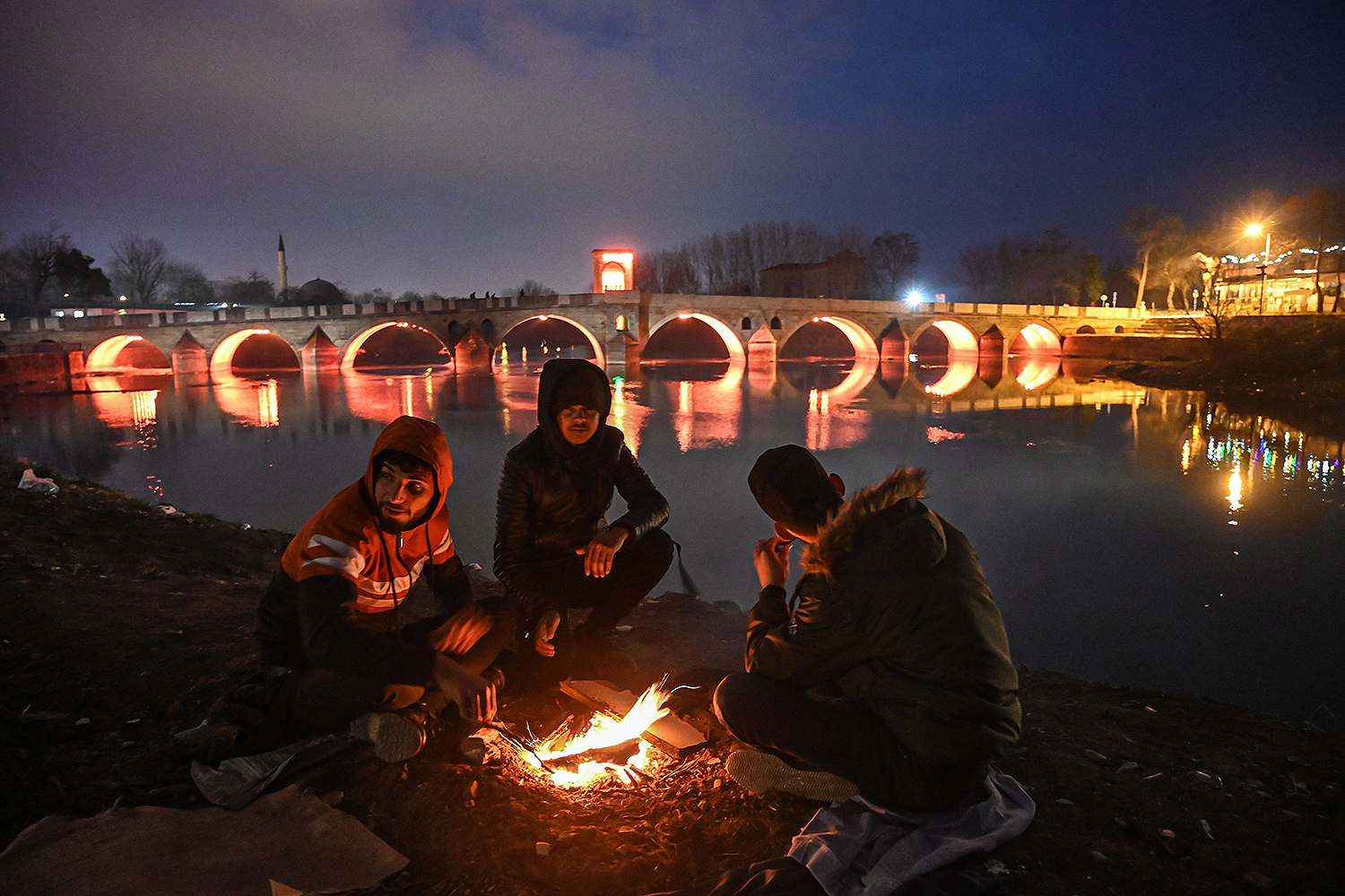 Migrants light a fire on the banks of the Tunca river in Edirne, Turkey, after an attempt to enter Europe at the Turkey-Greece border on March 5. Migrants and refugees hoping to enter Greece from Turkey fanned out across the border, maintaining pressure after Ankara declared its borders with the European Union open. OZAN KOSE/AFP via Getty Images