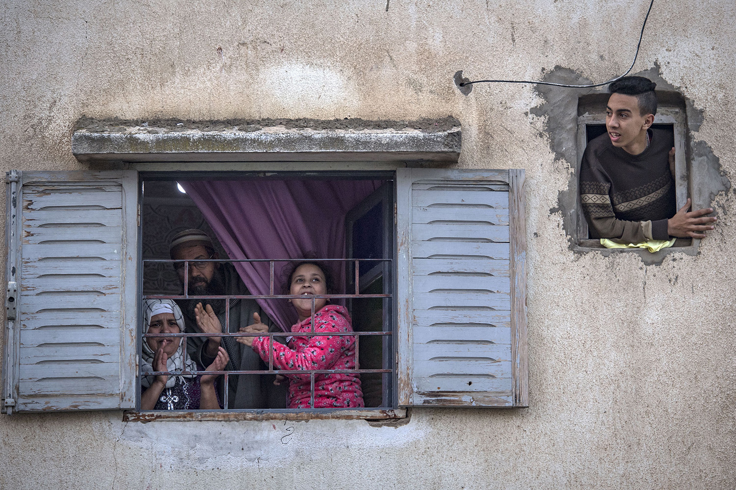 Moroccans confined at home in the Rabat district of Takadoum thank authorities from their windows as security forces and health workers instruct people to remain at home as a measure against the coronavirus pandemic on March 25. FADEL SENNA/AFP via Getty Images