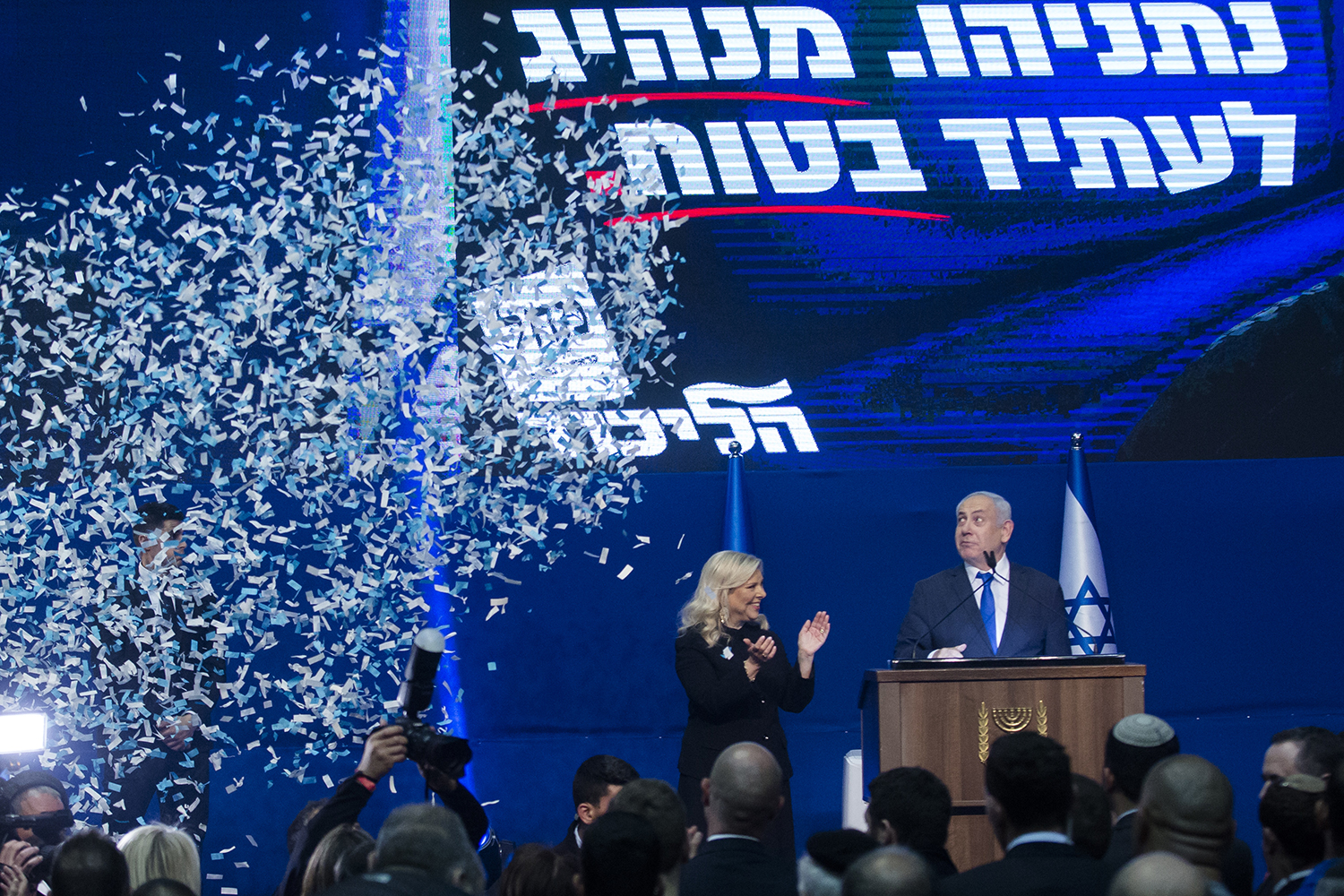 "Israeli Prime Minister Benjamin Netanyahu and his wife, Sara, thank supporters at the Likud party campaign headquarters in Tel Aviv early March 3 after polls officially closed. Netanyahu claimed ""a giant victory,"" boasting that his right-wing Likud party had defied ""all expectations"" in the country's third vote in less than a year. Amir Levy/Getty Images"