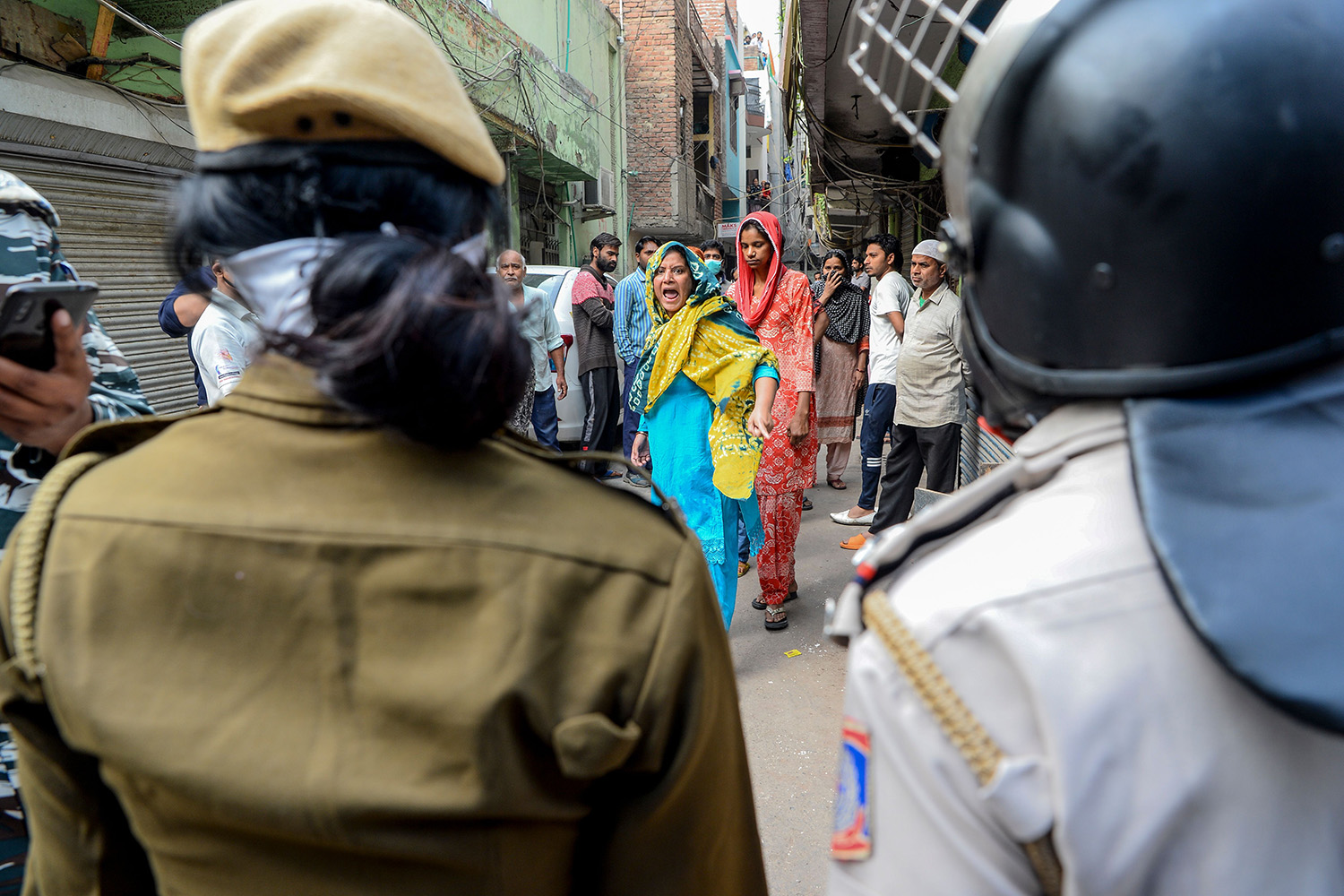 A woman shouts at security personnel patrolling the streets in the Shaheen Bagh neighborhood of New Delhi on March 24 after they removed demonstrators who were protesting against a new citizenship law. SAJJAD HUSSAIN/AFP via Getty Images