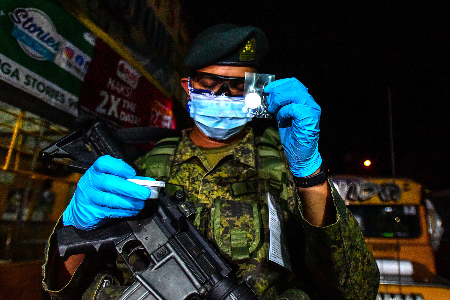 A member of the military takes Communion provided by the International Auxiliary Chaplaincy Association at a checkpoint in Manila, Philippines, as the city implements an enhanced community quarantine. MARIA TAN/AFP via Getty Images
