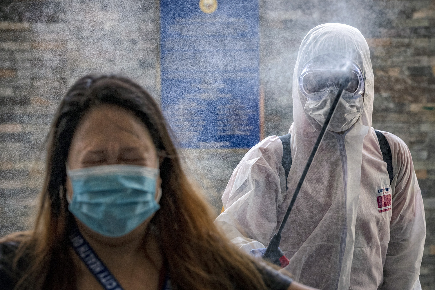 A government employee reacts as she is sprayed with disinfectant before entering an office building in Pasig City, Philippines, on March 19. Ezra Acayan/Getty Images
