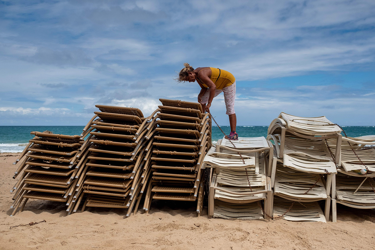Zaida Elena chains up beach chairs from her rental business in San Juan, Puerto Rico, on March 18. RICARDO ARDUENGO/AFP via Getty Images