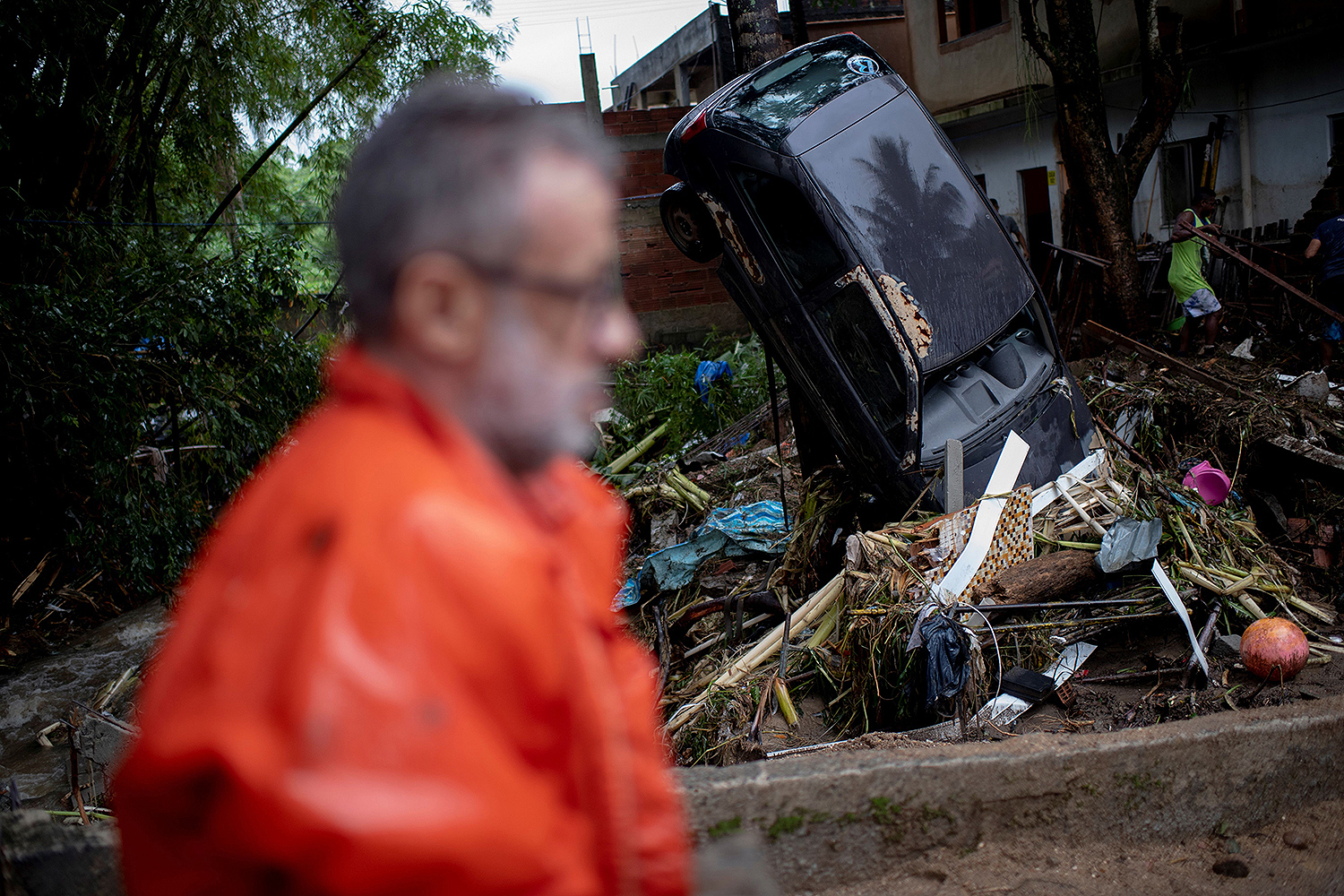 A man walks past damaged cars in the suburbs of Rio de Janeiro on March 2 following heavy rains. Downpours have swamped the area, leaving more than two dozen dead and thousands displaced, with more rain in the forecast. Mauro Pimentel/AFP via Getty Images