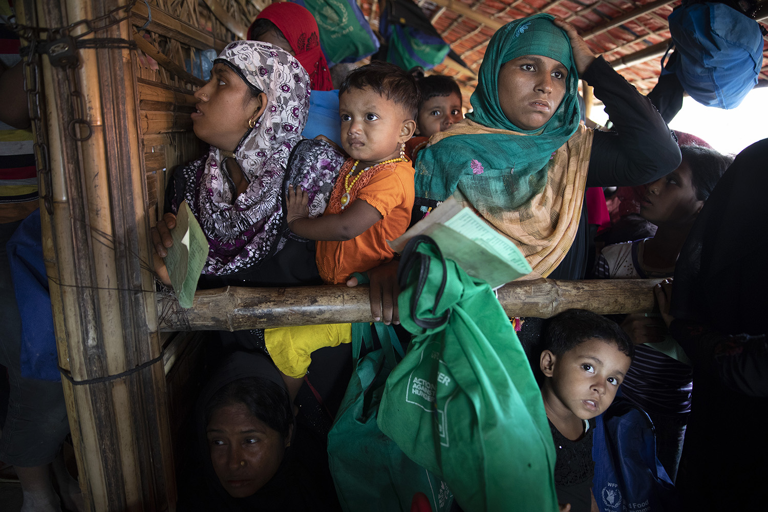 Rohingya women and children who fled Myanmar wait in line for food distribution in the Kutupalong camp in Cox's Bazar, Bangladesh, on Aug. 26, 2018.