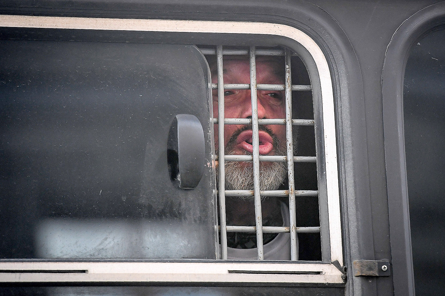 A detained protester speaks through the window of a police bus during an unsanctioned rally at the headquarters of the Federal Security Service in central Moscow on March 14. Moscow police detained dozens of people at a protest demanding that political prisoners be freed. YURI KADOBNOV/AFP via Getty Images