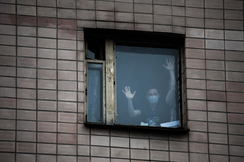 A student in a protective mask peers out of the window of a quarantined building at the St. Petersburg Medical Academy in St. Petersburg, Russia, on March 5.