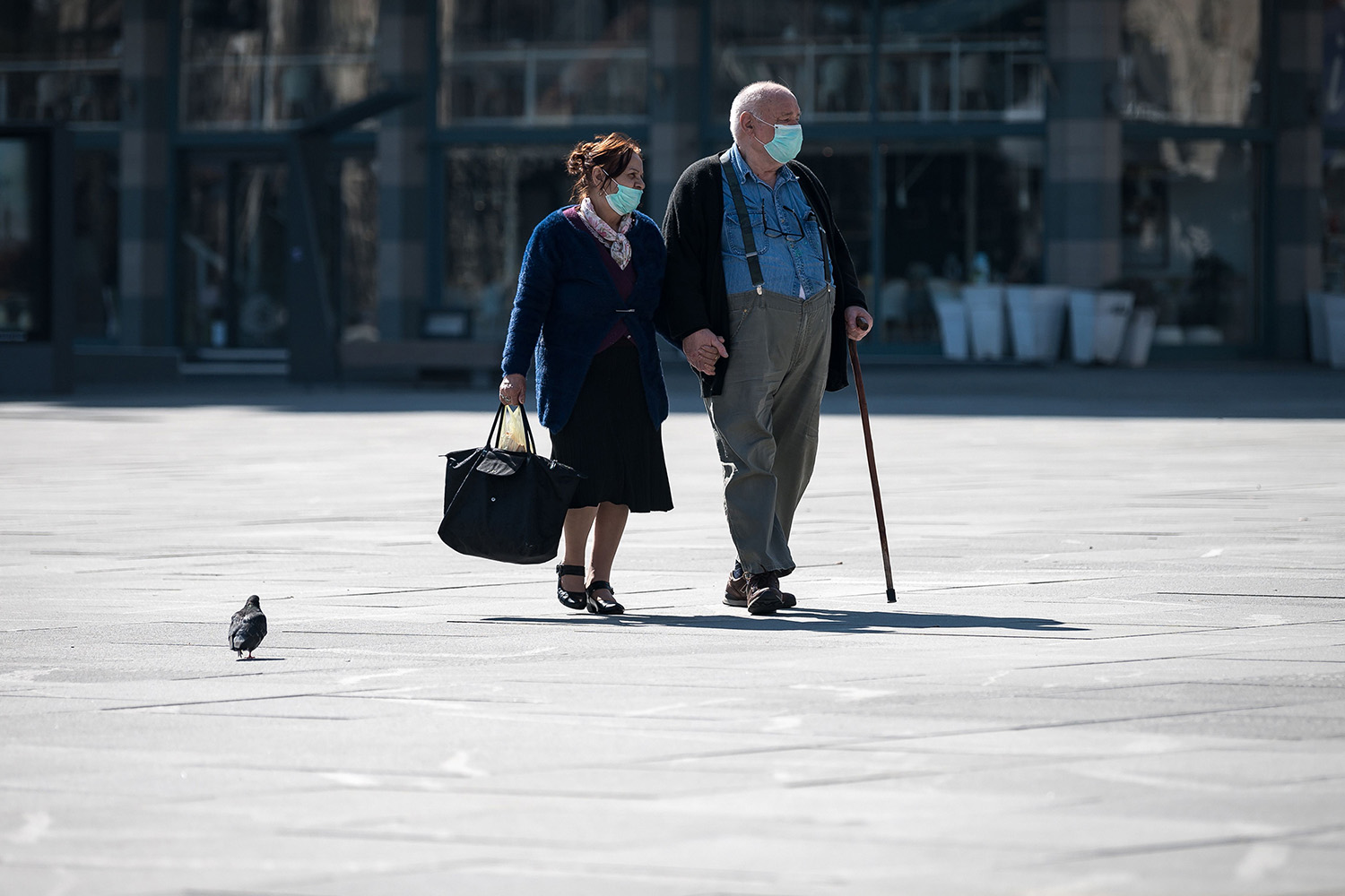 An elderly couple walk across Belgrade, Serbia's main square March 17. ANDREJ ISAKOVIC/AFP via Getty Images