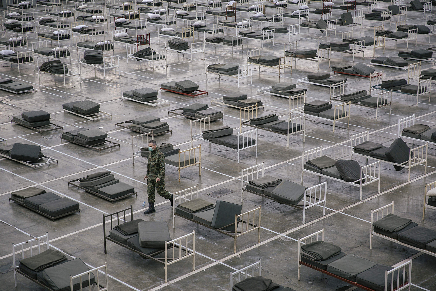 A Serbian member of the military walks March 24 among beds set up inside a hall at the Belgrade Fair to accommodate people suffering from mild symptoms of the coronavirus. VLADIMIR ZIVOJINOVIC/AFP via Getty Images
