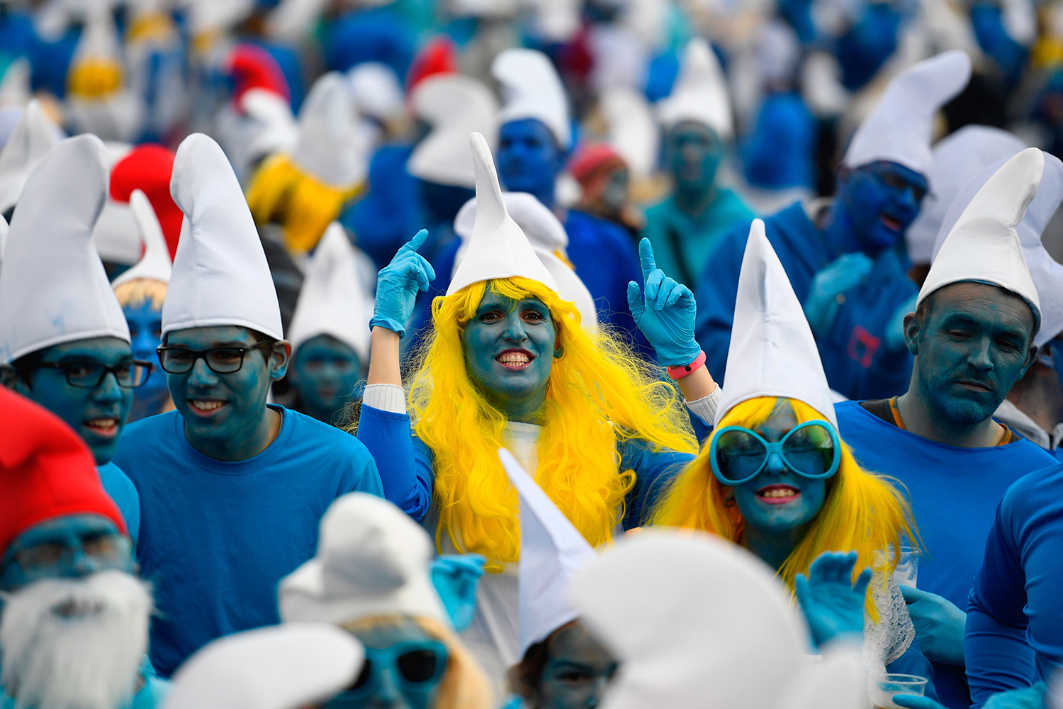 "People dressed as Smurfs (""Schtroumpfs"" in French) attend a world-record gathering of the cartoon characters in Landerneau, western France, on March 7. DAMIEN MEYER/AFP via Getty Images"