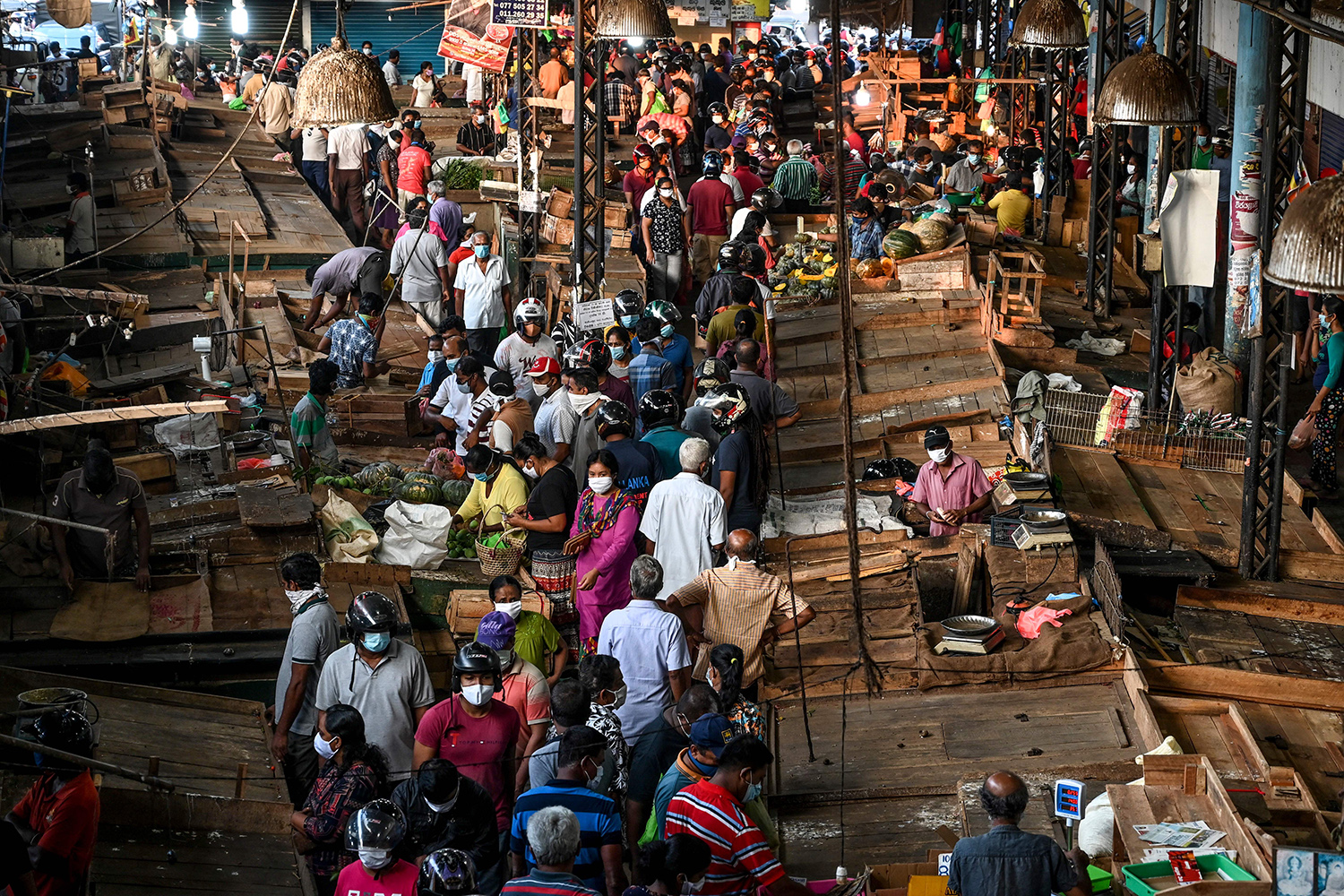 People buy supplies at a vegetable market in Piliyandala, a suburb of Colombo, Sri Lanka, on March 24 as authorities briefly lift a curfew to allow residents to stock up on essentials. LAKRUWAN WANNIARACHCHI/AFP via Getty Images