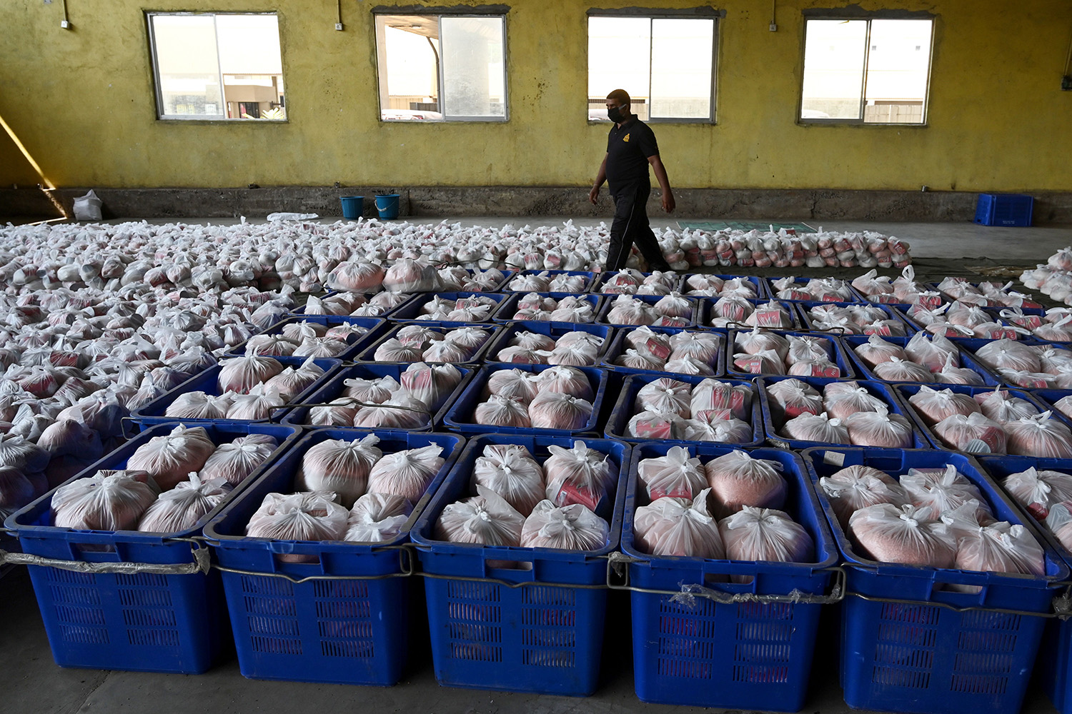 A member of the Sri Lanka Civil Security Force walks among packages of dry rations of food and commodities to be distributed at a warehouse near Colombo on March 25. LAKRUWAN WANNIARACHCHI/AFP via Getty Images