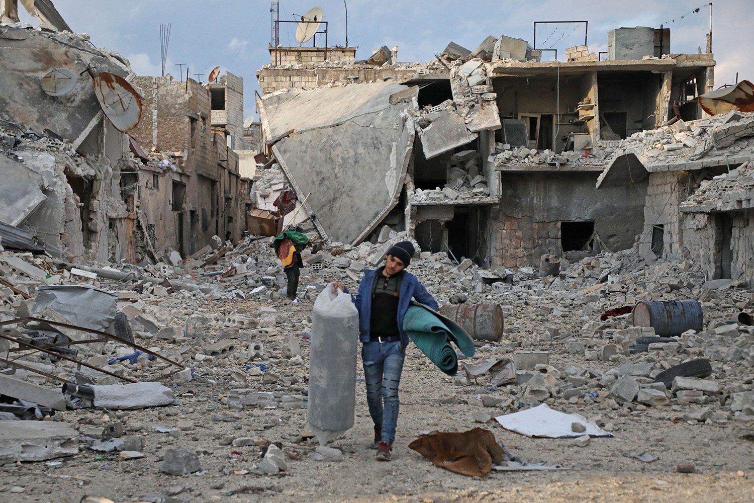 Syrians salvage some of their belongings from the rubble of houses as they prepare to flee the town of Atareb in the rebel-held western countryside of Syria's Aleppo province on Feb. 22. NAYEF AL ABOUD/AFP via Getty Images
