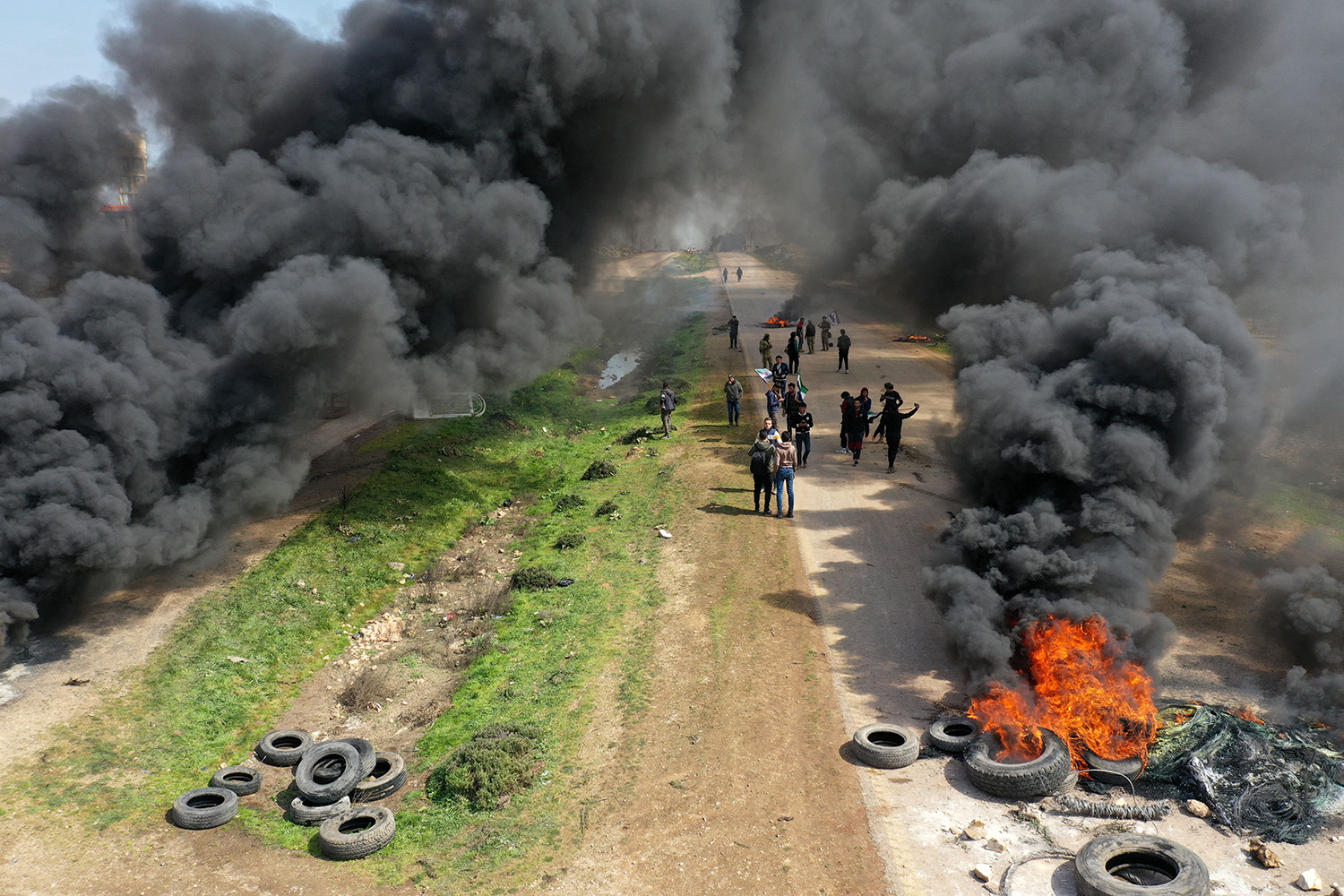 Syrian protesters burn tires in the village of Al-Nayrab in northwestern Syria on March 15 in an attempt to block traffic on the strategic M4 highway and prevent a joint Turkish-Russian military patrol from being conducted. OMAR HAJ KADOUR/AFP via Getty Images