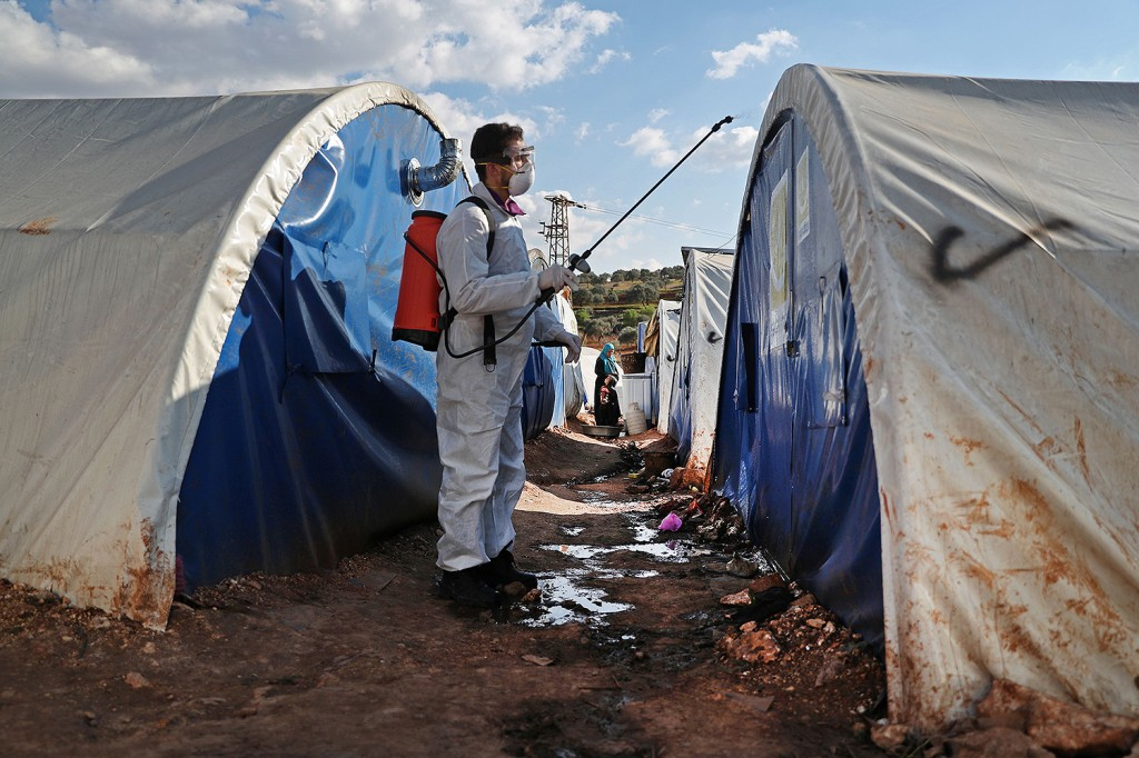 A member of the Syrian relief group Violet Organization disinfects tents