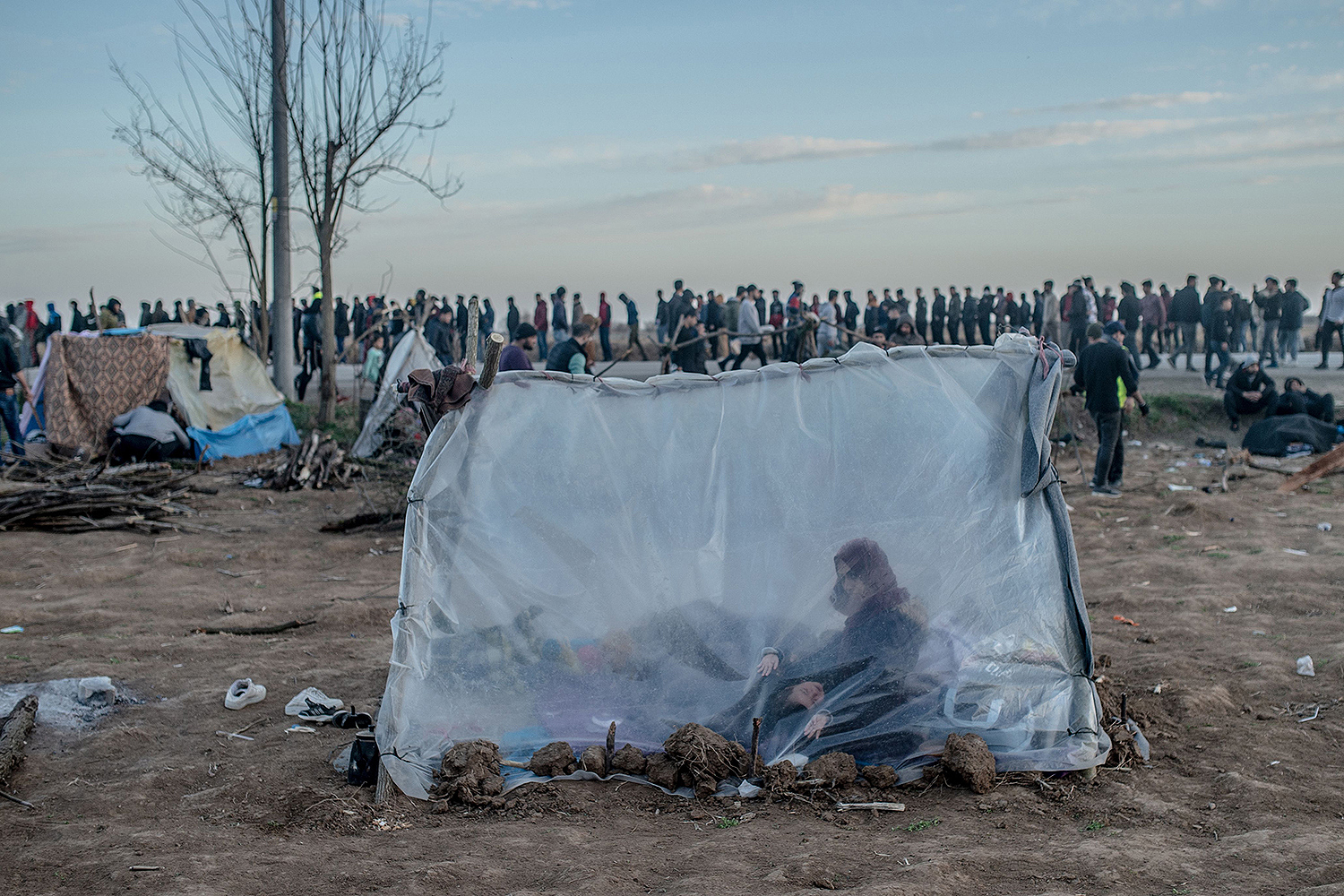 A Syrian woman sits in a tent with her son as others wait for food distribution March 3 in Edirne, Turkey, near the Pazarkule border crossing to Greece.  BULENT KILIC/AFP via Getty Images