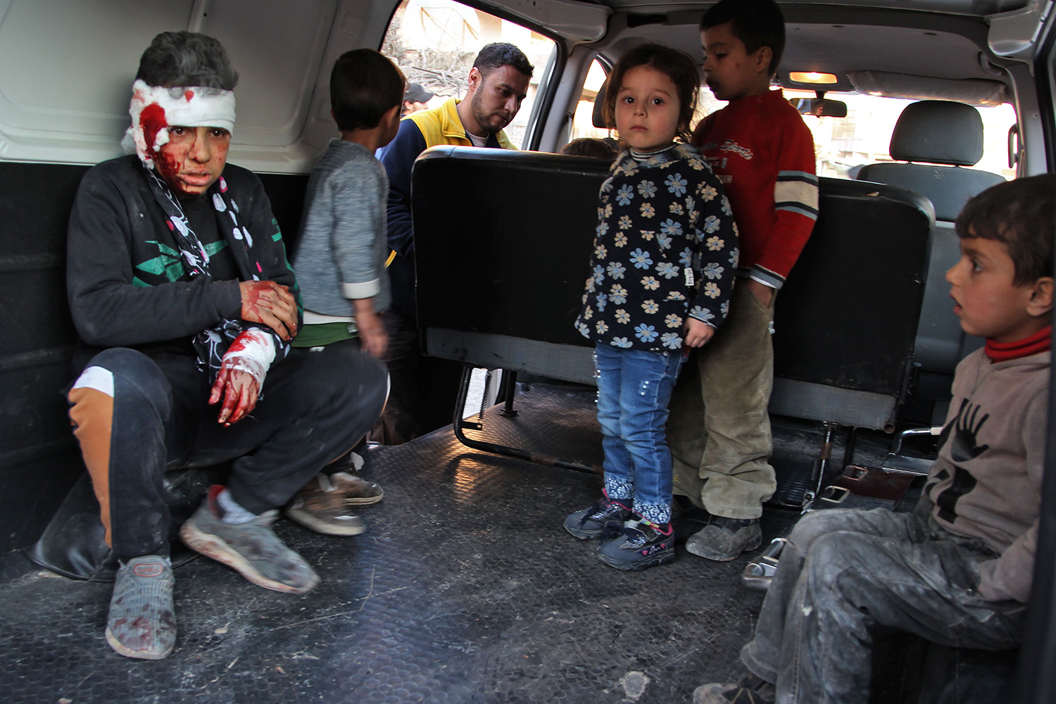 Syrian children sit inside a vehicle as they are evacuated from the scene of a pro-regime forces air strike in Maarrat Misrin in Syria's northwestern Idlib province on Feb. 25. ABDULAZIZ KETAZ/AFP via Getty Images