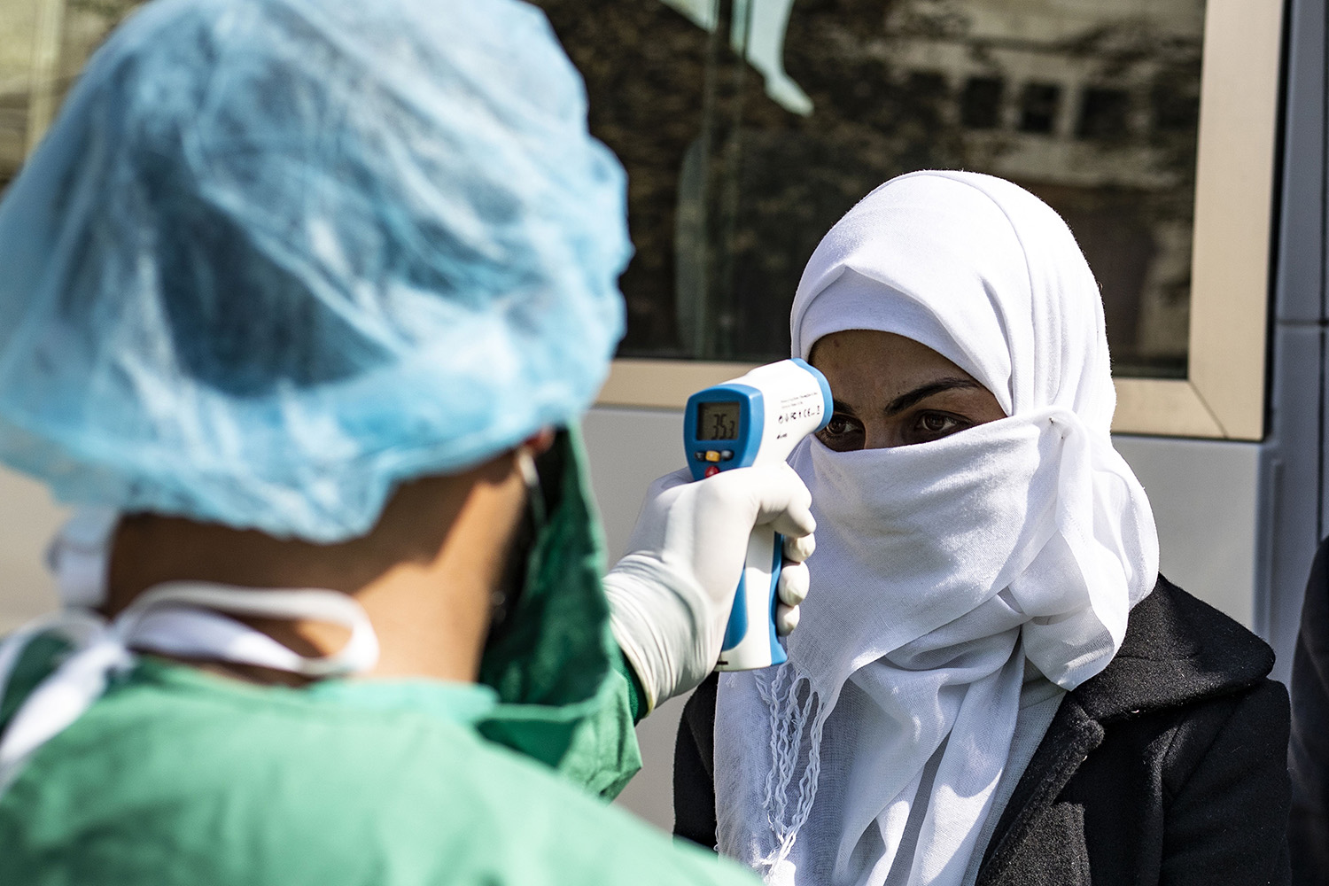 A medic checks the body temperature of a passenger, as a preventive measure against the coronavirus, upon her arrival by bus in Syria's Kurdish area from Iraqi Kurdistan via the Semalka border crossing in northeastern Syria on Feb. 26. DELIL SOULEIMAN/AFP via Getty Images
