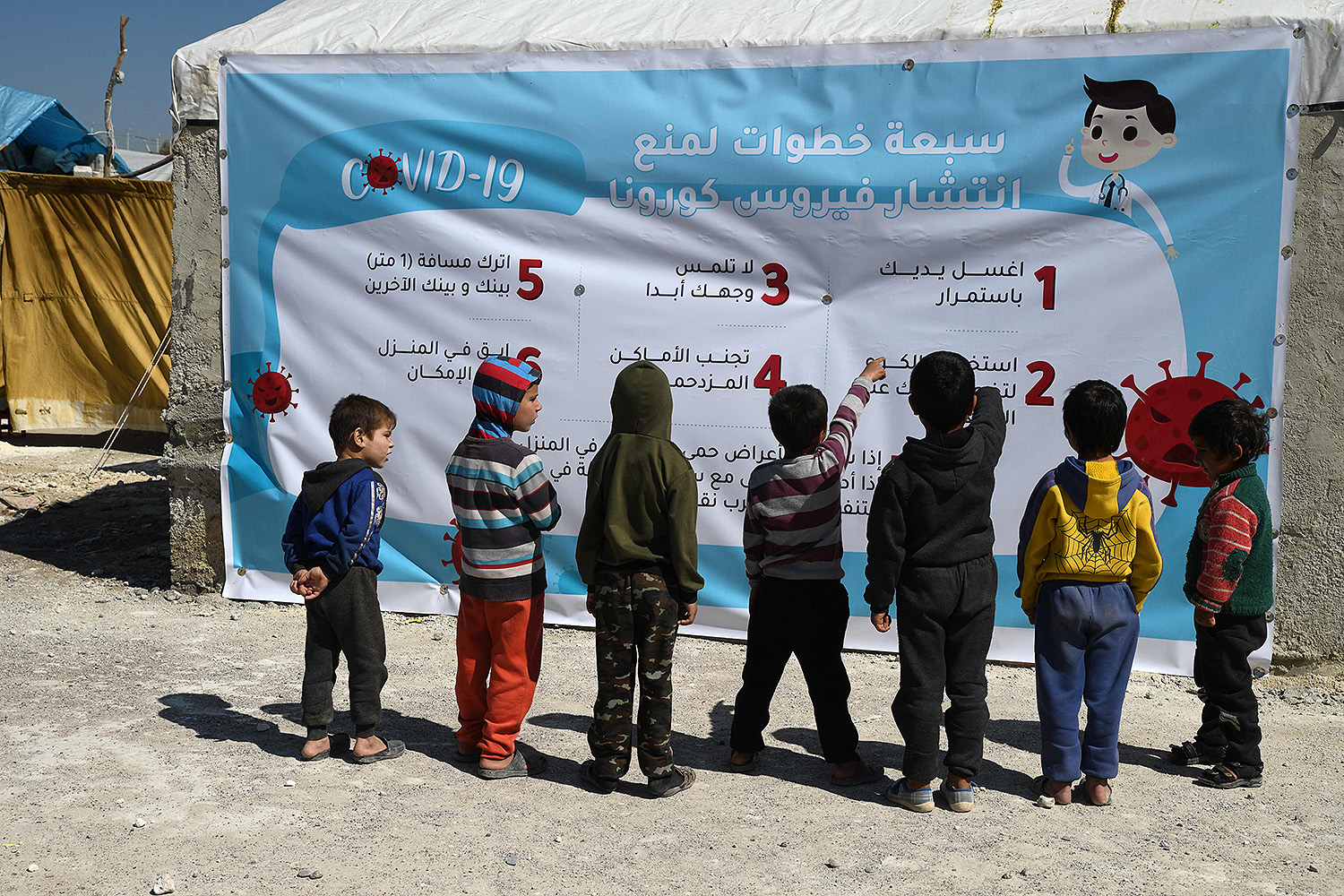 Displaced Syrian children read a poster outlining the seven steps to prevent the spread of coronavirus at a camp for the internally displaced near the Turkish border in the rebel-held part of Aleppo on March 22. RAMI AL SAYED/AFP via Getty Images