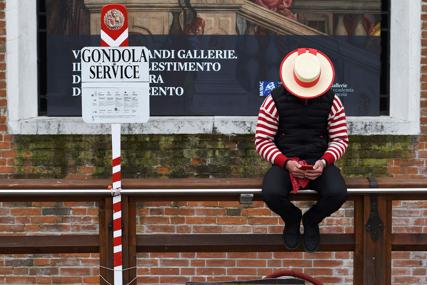 A gondolier checks his phone while waiting for tourists in Venice, Italy, on March 5. ANDREA PATTARO/AFP via Getty Images