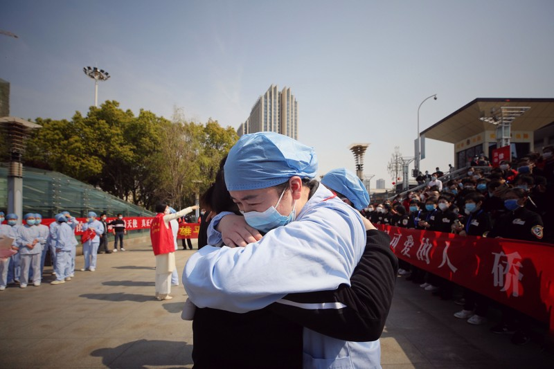 Medical assistance teams from across China leave Wuhan as the number of new coronavirus infections drops. At a farewell ceremony March 19, a Wuhan medical worker (right) embraces a member of a Jiangsu medical assistance team who helped with the recovery effort. STR/AFP via Getty Images