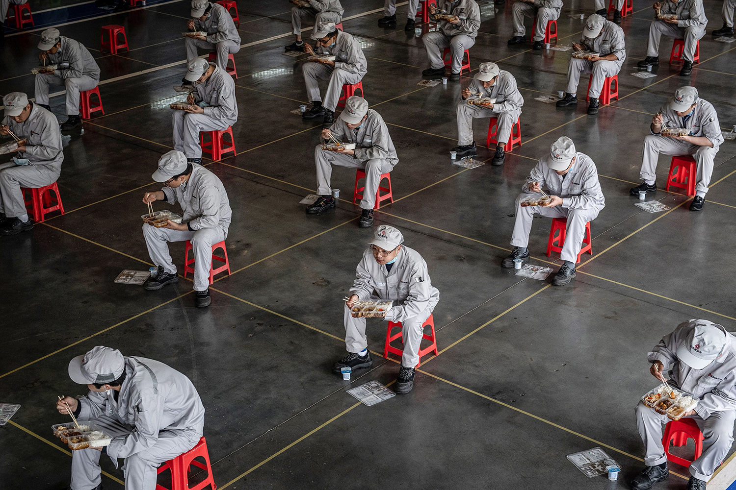 Employees practice social distancing while eating lunch on their break at the Dongfeng Honda auto plant in Wuhan, China, on March 23. STR/AFP via Getty Images