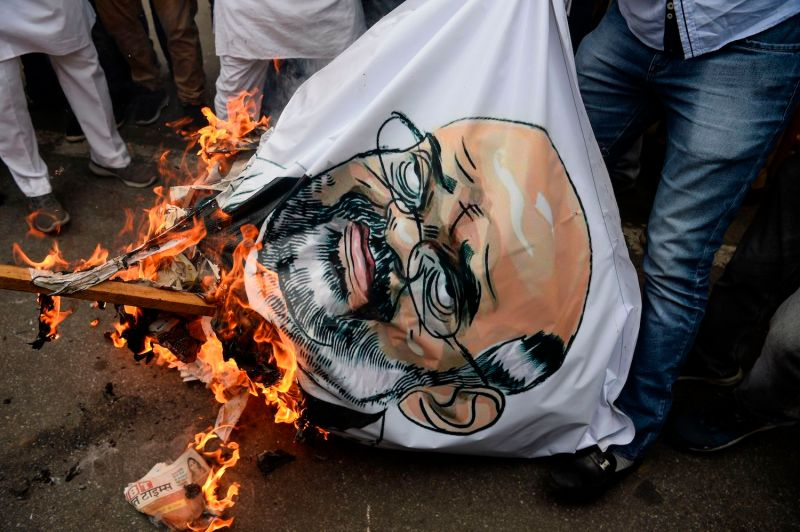 Protesters burn an effigy of Indian Home Minister Amit Shah during a protest demanding his resignation.