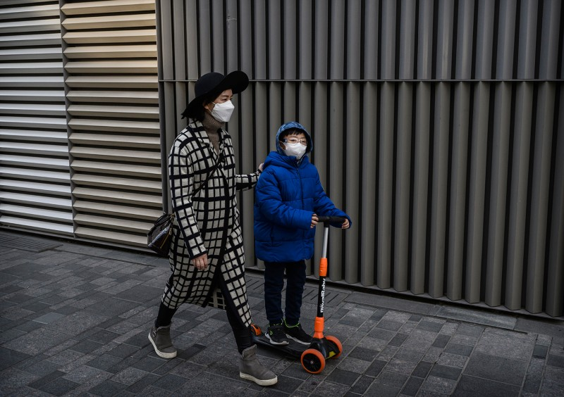A boy rides a scooter as he walks with his mother on March 10 in Beijing.
