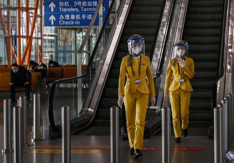 Chinese tourist information clerks wear protective masks and visors in the arrivals area at Beijing Capital International Airport on March 24.