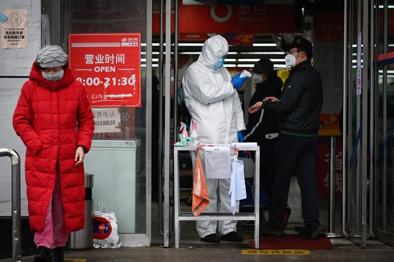 A staff member checks the temperature of a customer at the entrance of a supermarket in Beijing on Feb. 29.