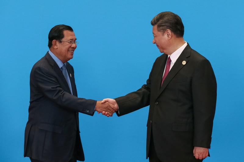 Chinese President Xi Jinping shakes hands with Cambodian Prime Minister Hun Sen