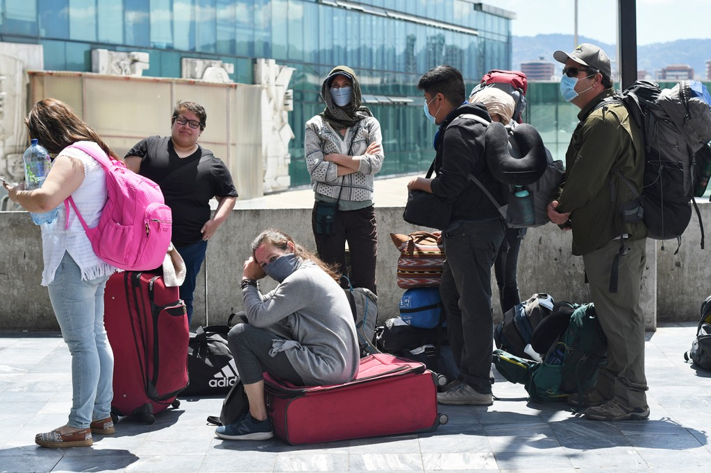 Travelers wait for a charter flight arranged by the U.S. Embassy
