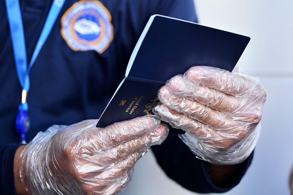 A security agent wearing plastic gloves checks a U.S. passport outside the Toncontin International Airport in Tegucigalpa, Honduras, on March 15.