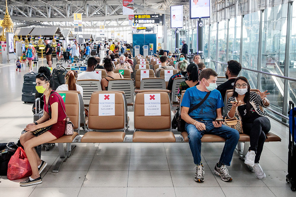 People wait on seats marked where they are and aren't permitted to sit in order to observe social distancing rules at Suvarnabhumi Airport in Bangkok, Thailand, on March 25.