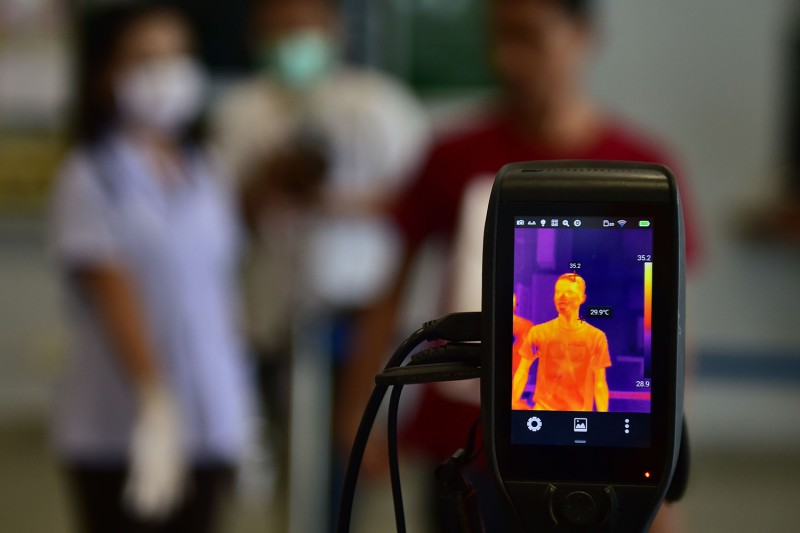 A thermal camera monitor shows the body temperatures of a man at the customs checkpoint in Sungai Kolok, Thailand