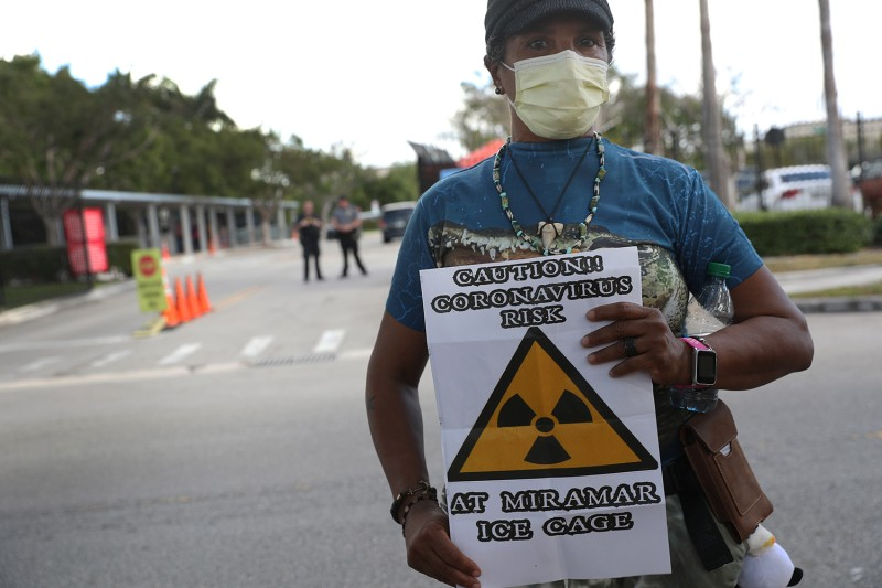 "Odalys K. Fernandez holds a sign reading, ""Caution!! Coronavirus risk at Miramar ICE cage"", as she joins protesters outside a U.S. Immigration and Customs Enforcement office in Miramar, Florida, on March 13."