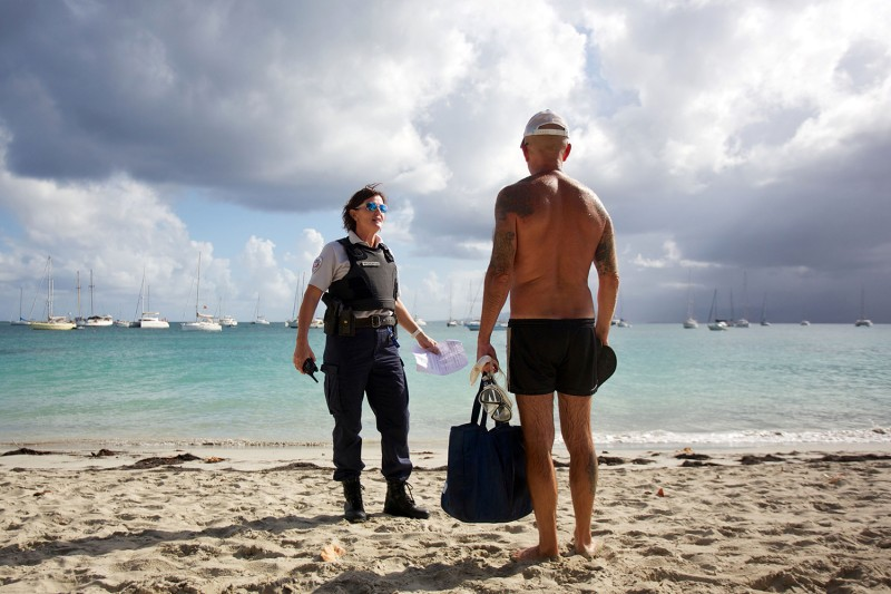 A French police officer speaks to a man as she patrols on the Datcha beach after its closure to stop the spread of the coronavirus on the French overseas island of Guadeloupe on March 20.
