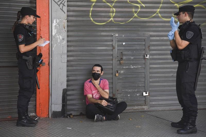 Police warn a young man for not complying with the mandatory quarantine to stay home to stem the spread of the coronavirus in Buenos Aires on March 20. Mariano Gabriel Sanchez/Anadolu Agency via Getty Images