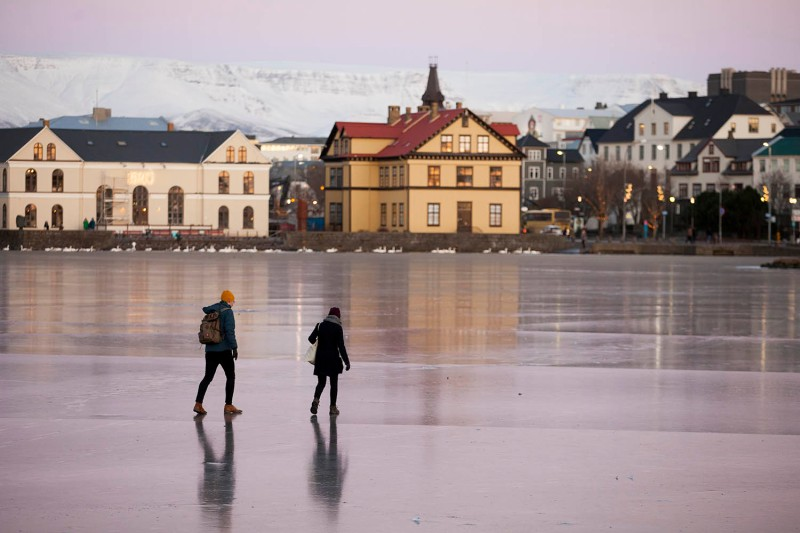 People walk across frozen Tjornin, a lake in Reykjavik, Iceland, on Dec. 7, 2017.