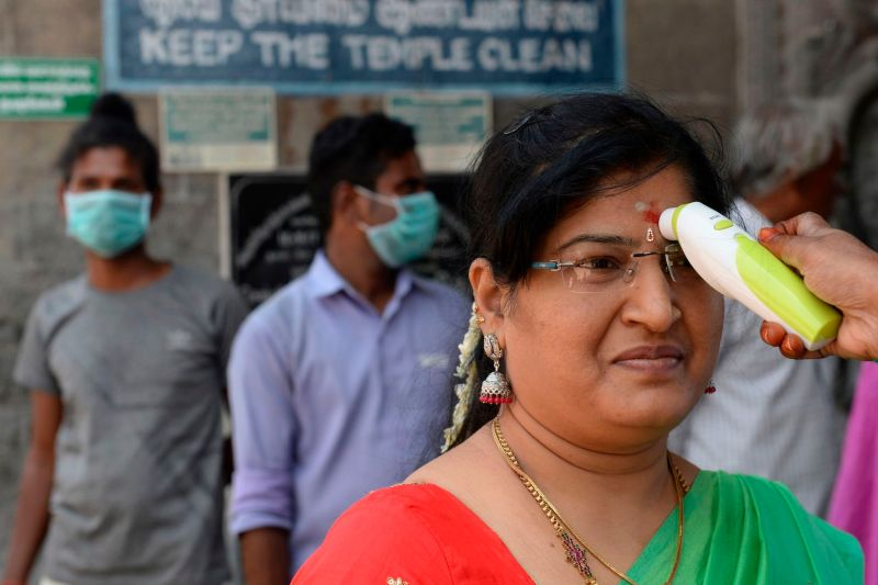 A health worker checks the body temperature of a woman amid concerns over the spread of the coronavirus at Kapaleeshwar temple.