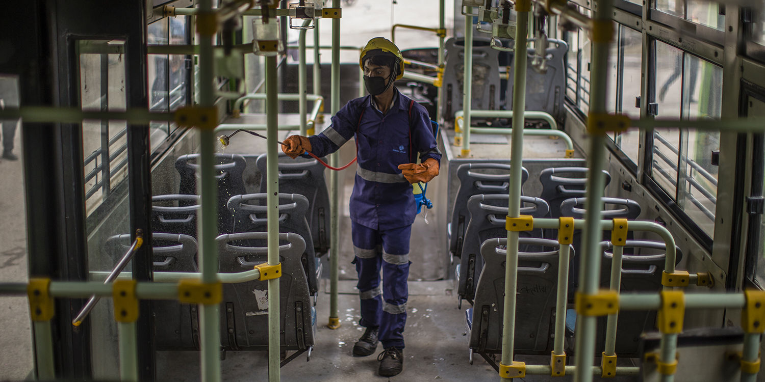 An Indian health worker wearing a protective suit sprays disinfectant inside a Delhi Transport Corporation bus to help stem the spread of the coronavirus in New Delhi on March 15.