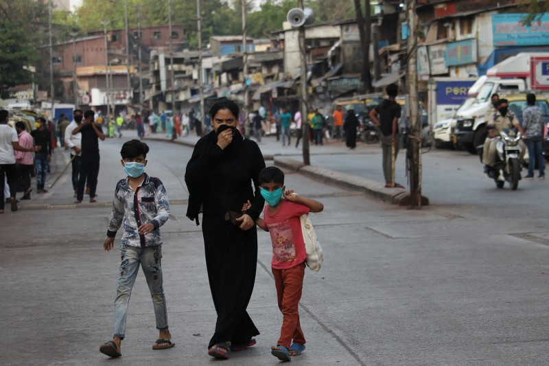 A woman walks with children wearing protective masks during a curfew in response to the outbreak of the coronavirus pandemic in Mumbai, India, on March 24.