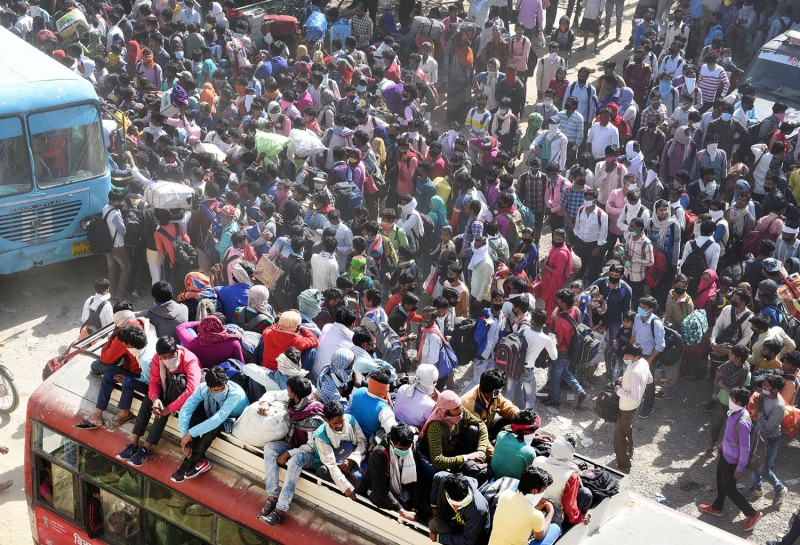 Migrant workers surround buses amid the nationwide lockdown to stem the spread of coronavirus at Lal Kuan bus stand in Ghaziabad, India, on March 29.